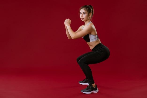 赤い壁にフィットネスで運動するスポーツの黒い服を着た若い女性