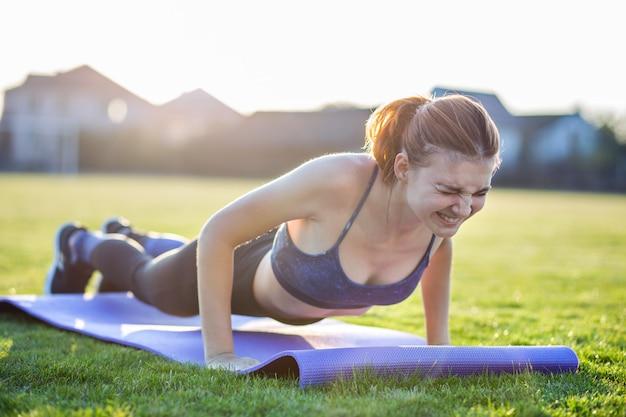 Молодая женщина в спортивной одежде, обучение в поле на рассвете. Premium Фотографии