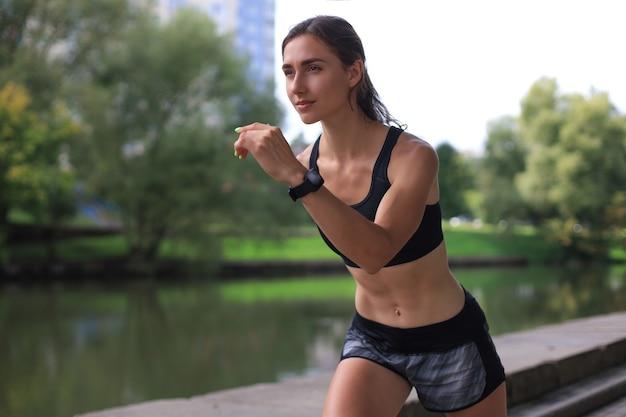 야외에서 운동하는 동안 달리는 스포츠 의류를 입은 젊은 여성.