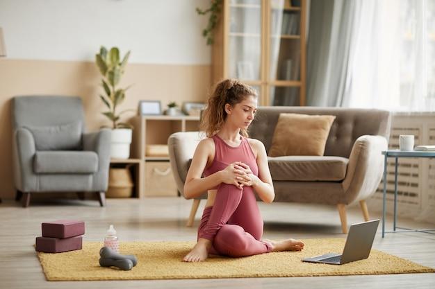 Молодая женщина в спортивной одежде сидит на полу, смотрит онлайн-уроки фитнеса на ноутбуке и делает упражнения дома