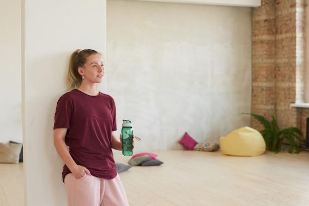 그녀는 훈련 후 쉬고 물 한 병 댄스 스튜디오에 서있는 스포츠 의류에 젊은 여자