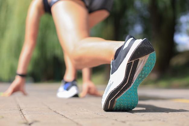 야외에서 달리는 동안 출발선에 서 있는 스포츠 의류를 입은 젊은 여성.