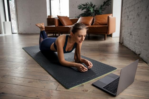 自宅で板の運動をし、ラップトップでビデオを見て、指示を繰り返すスポーツユニフォームの若い女性。高品質の写真