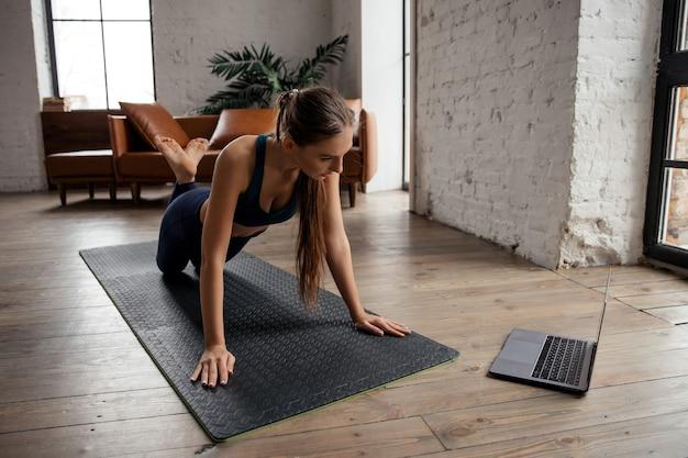 自宅の居間で板の運動をし、ラップトップコンピューターでビデオを見て、オンラインの指示を繰り返すスポーツユニフォームの若い女性。高品質の写真