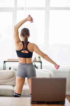 집에서 운동복에 젊은 여자, 노트북에서 온라인 맞춤 교육