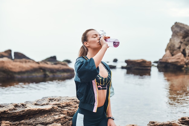 ビーチの動機で石の上に座って水を飲むスポーツウェアの若い女性