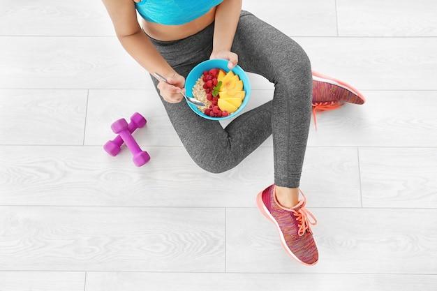 Молодая женщина в спортивной одежде ест овсянку, сидя на полу