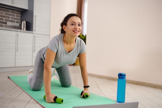 집에서 하루 동안 피트니스 매트에서 운동하는 운동복에 젊은 여자