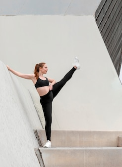 Молодая женщина в спортивной одежде, упражнения на открытом воздухе