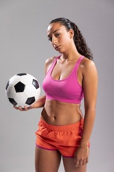 Молодая женщина в спортивной одежде держит мяч