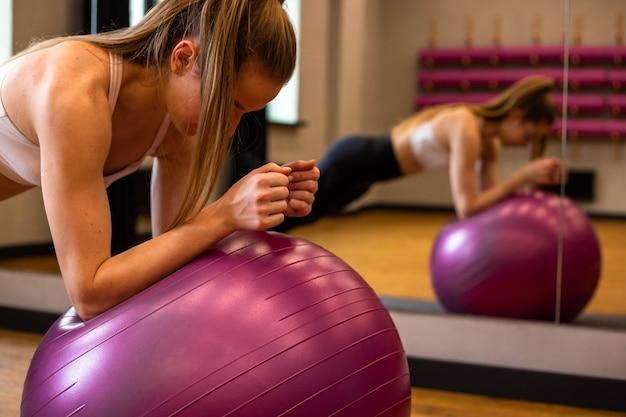 スポーツウェアの若い女性は、屋内ジムでフィットボールに従事しています