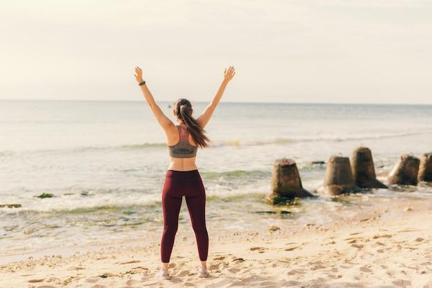 スポーツウェアの若い女性は、自由のために立って腕を上げています。