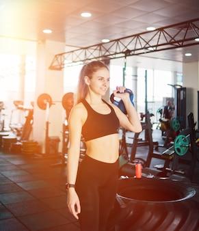 スポーツウェアの若い女性は、ジムに立っている片手でケトルベルを持ち上げます。ファンクショナルトレーニング