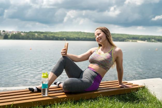 朝のスポーツトレーニング後に休んでいるスポーツウェアの若い女性