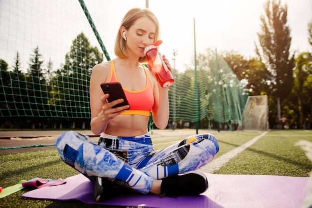 Молодая женщина в спортивной одежде сидит на коврике, пьет воду из бутылки, использует смартфон и расслабляется после спортивных упражнений