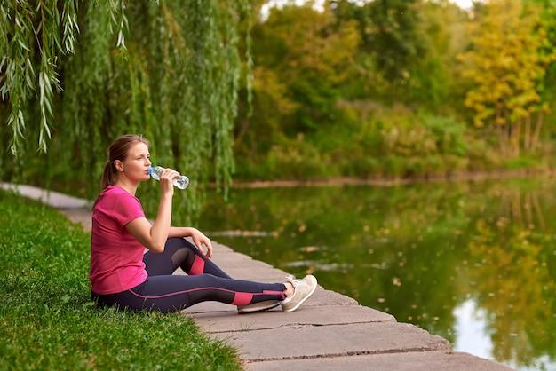 운동복을 입은 젊은 여성이 공원의 강둑에 앉아 물을 마신다