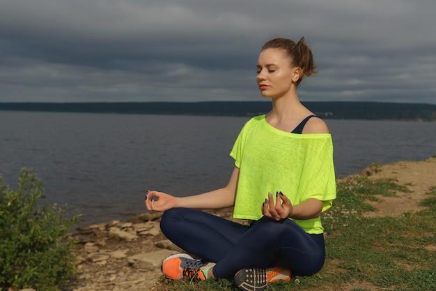 강가에 앉아 운동복에 젊은 여자