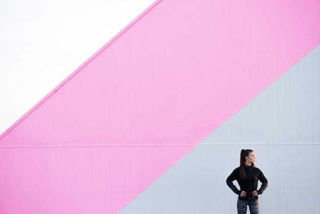 Молодая женщина в спортивной одежде стоит возле красочной стены