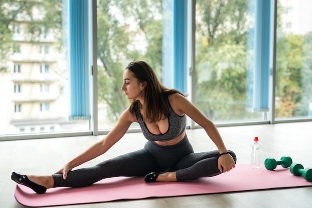 Молодая женщина в спортивной растяжке практикующих йогу на коврике в помещении в классе. концепция образа жизни здравоохранения