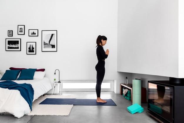 ナマステの手と自宅でのヨガの練習中に瞑想するスポーツウェアの若い女性