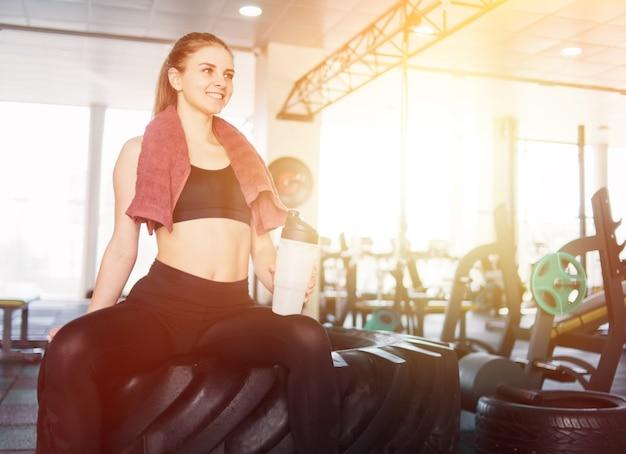 水のボトルを保持し、ジムでの機能トレーニングのために大きなホイールで休んで座っている彼女の首にタオルを持ったスポーツウェアの若い女性