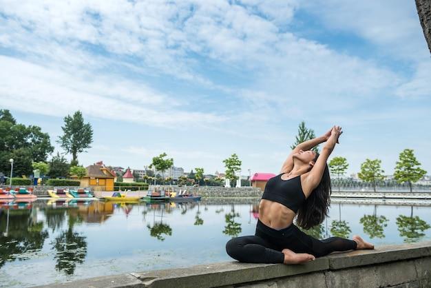 湖の近くで屋外でフィットネス運動をしているスポーツウェアの若い女性。健康ライフスタイル