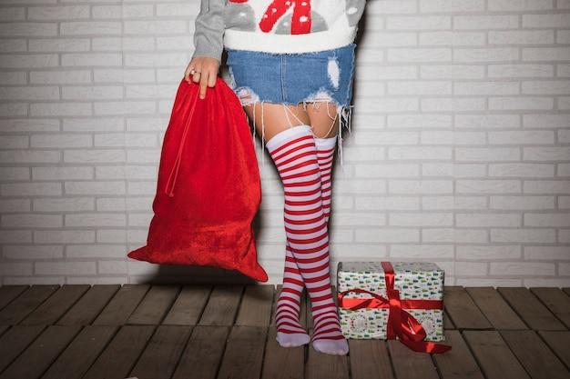 Молодая женщина в чулках с рождественским подарком коробка и сумка