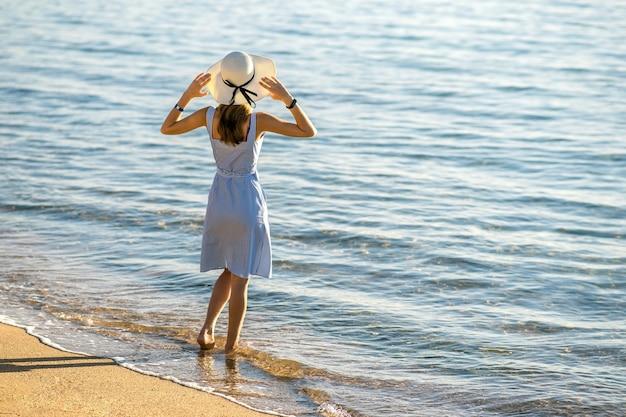 Молодая женщина в соломенной шляпе и платье, стоя отдельно на пустом песчаном пляже на берегу моря. одинокая туристическая девушка, смотрящая на горизонт над спокойной поверхностью океана в отпуске.