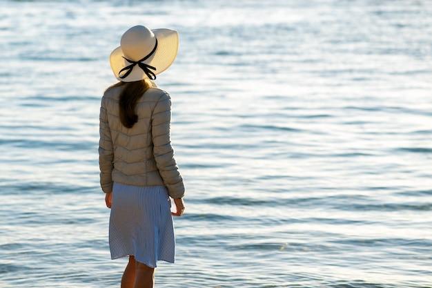 麦わら帽子と海岸の空の砂浜に一人で立っているドレスの若い女性。休暇旅行で穏やかな海面の地平線を見ている孤独な観光客の女の子。