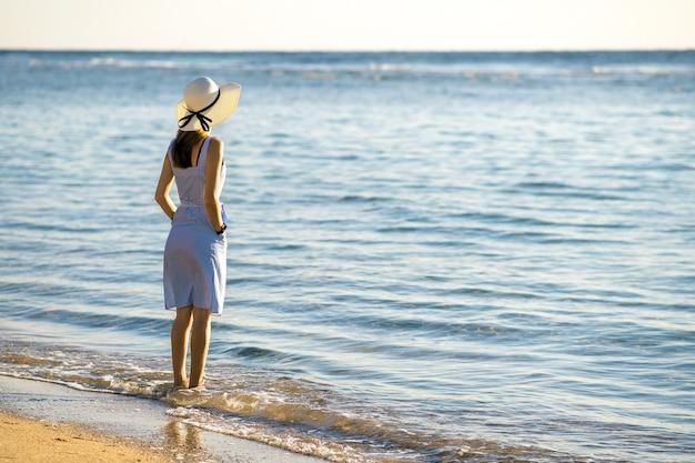 Молодая женщина в соломенной шляпе и платье, стоя отдельно на пустом песчаном пляже на берегу моря.