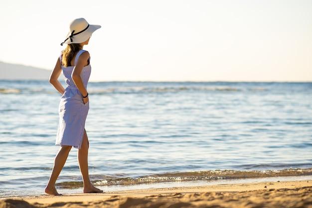 麦わら帽子とドレスを着た若い女性が海岸の空の砂浜を一人で歩いています。休暇旅行で穏やかな海面の地平線を見ている孤独な観光客の女の子。
