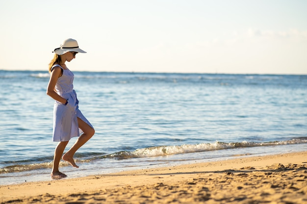 麦わら帽子と海岸の空の砂浜で一人歩きのドレスの若い女性。休暇旅行で穏やかな海の表面の地平線を見て孤独な観光女の子。