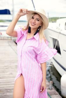夏に桟橋で休んでいる麦わら帽子とピンクのドレスの若い女性