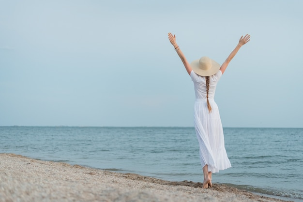 Молодая женщина в соломенной шляпе и белом платье гуляет по пляжу.