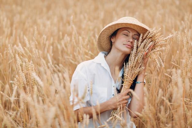 農業分野で小麦の穂の束を保持している麦わら帽子の若い女性