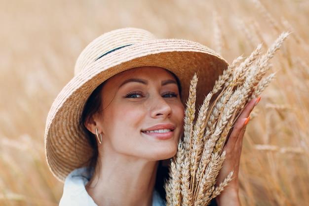 Молодая женщина в соломенной шляпе, держа сноп колосьев пшеницы на сельскохозяйственном поле.