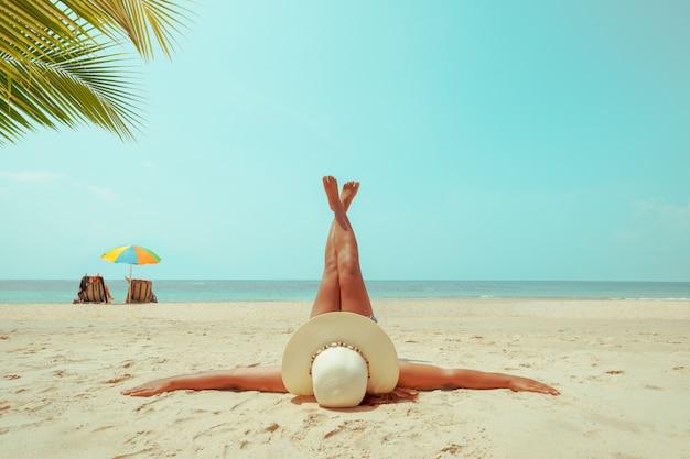 熱帯のビーチで日光浴横になっている麦わら帽子の若い女性。