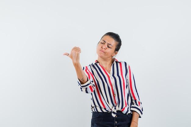 Молодая женщина в полосатой блузке делает вид, будто держит телефон в руке, смотрит на него и смотрит сосредоточенно