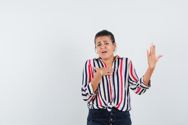 Молодая женщина в полосатой блузке делает вид, будто держит телефон в руке, указывает на себя и выглядит серьезным
