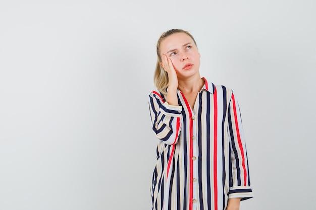 Молодая женщина в полосатой блузке кладет руку на щеки и думает о чем-то и выглядит сомнительно