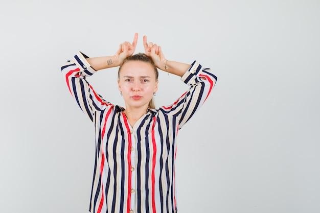 Молодая женщина в полосатой блузке показывает жест неудачника и выглядит грустной