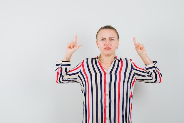 Молодая женщина в полосатой блузке показывает знак проигравшего и выглядит грустной