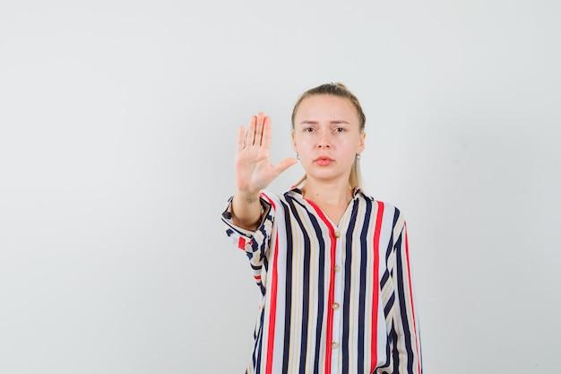 Молодая женщина в полосатой блузке показывает жест стоп и выглядит сердитой