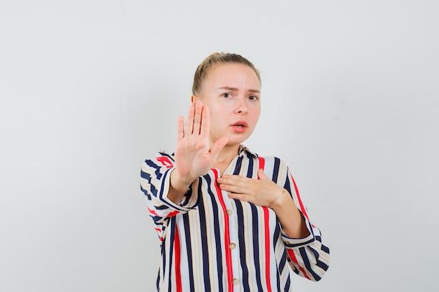 Молодая женщина в полосатой блузке показывает жест стоп и выглядит испуганной