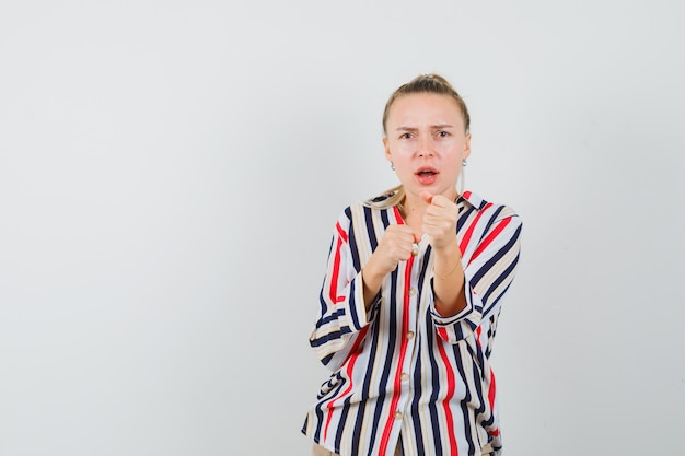 誰かと戦おうとして怒っているように見える縞模様のブラウスの若い女性