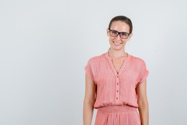縞模様のドレス、メガネ、陽気に見える若い女性。正面図。