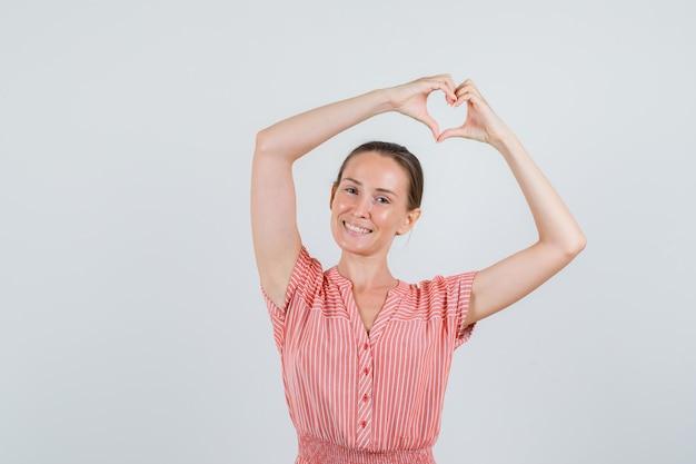 Молодая женщина в полосатом платье делает форму сердца руками и выглядит весело, вид спереди.