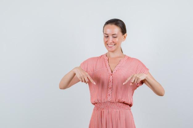 Молодая женщина в полосатом платье, указывая вниз и весело, вид спереди.