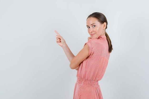 Молодая женщина в полосатом платье указывая вверх, оглядываясь назад и глядя рад.