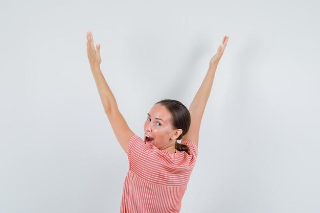 振り返って幸せそうに見えながら、腕を上げる縞模様のドレスの若い女性、背面図。